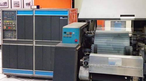 "The IBM 1403 printer generating a Mandelbrot set on standard 14 7/8""×11"" green-bar paper. The IBM 1401 computer is at the left."