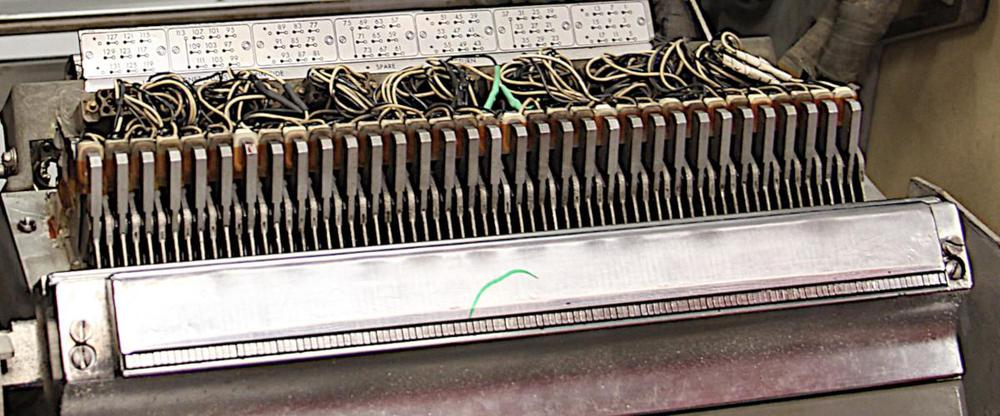 A hammer bank in the IBM 1403 printer. At the bottom, the impact points for the 132 hammers (one for each column) are visible. The coils and wiring for 1/4 (33) of the 132 hammers are visible at the top.