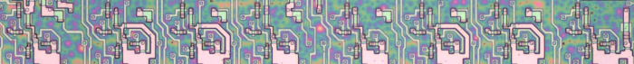 The ACT register in the 8085. This image shows the silicon that implements the 8-bit register. Each of the large pink structures is one bit.  Bit 7 is on the left and bit 0 on the right.