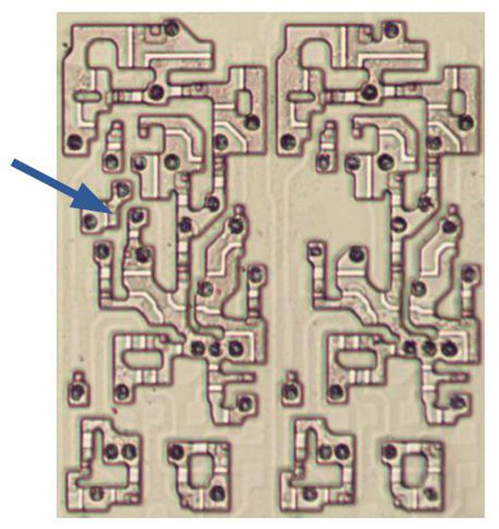 These two stages of the 8086's adder are almost identical, except for the circuitry indicated by the arrow. In this photo, the metal and polysilicon layers were removed, showing the underlying silicon.