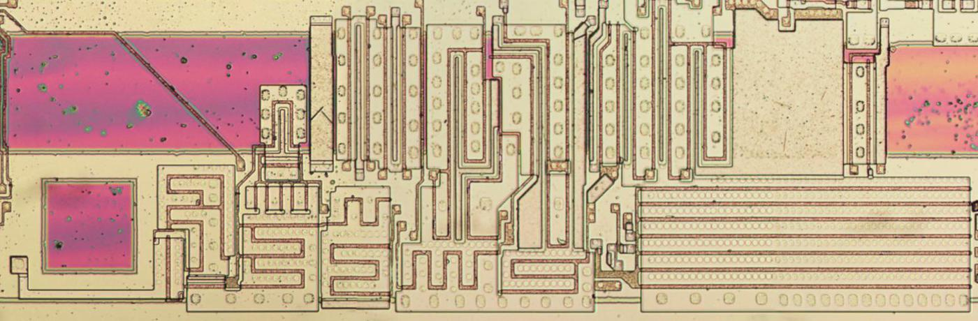 The clock driver circuitry on the die. The metal has been removed, revealing the large transistors in the circuit. The clock input pin is the purple square on the left.