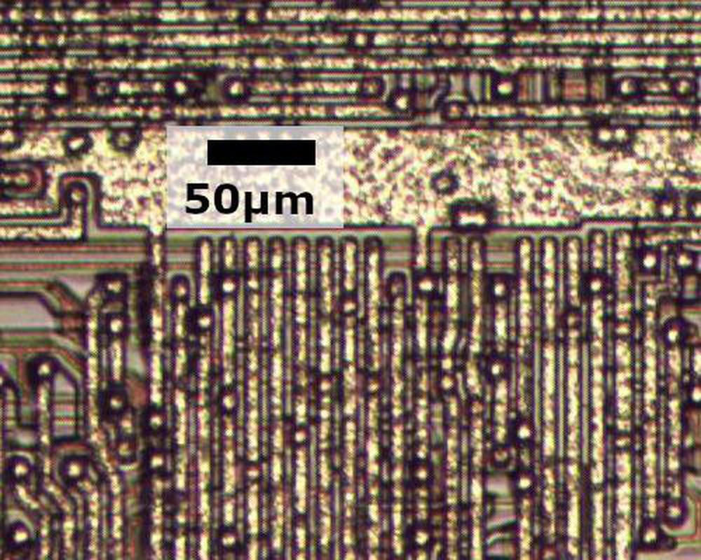 The metal layer of the older 8086 chip. Reddish polysilicon wiring is visible underneath the metal.