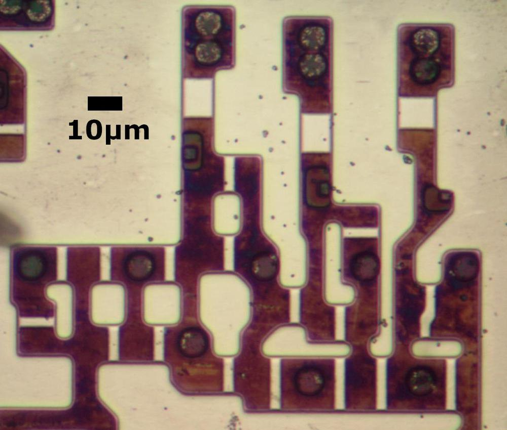 Transistors in the older 8086 chip. The metal and polysilicon were removed for this photo. Circles are vias that connect to the metal layer.