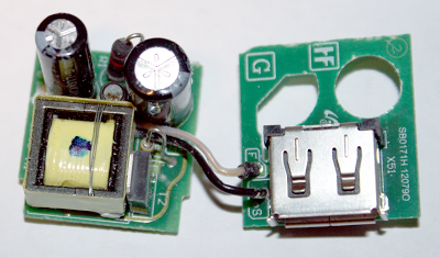 Circuit boards of a Samsung cube USB charger, showing the transformer, switching transistor, filter capacitors, and other large components