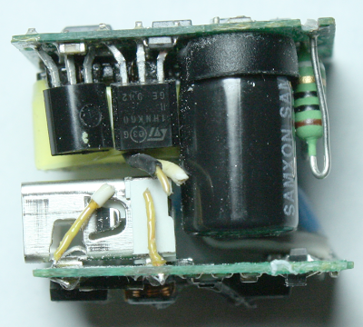 Inside the iPhone charger. Switching transistors, filter capacitor, and fusible resistor are on top. USB connector on bottom. Transformer wires were cut for disassembly.