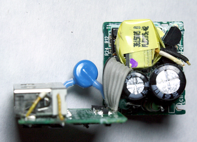 The secondary (left) and primary (right) circuit boards of the Apple iPhone charger. Note the The flyback transformer (yellow), Y capacitor (blue), filter capacitors (black cylinders), and USB connector (silver on left)
