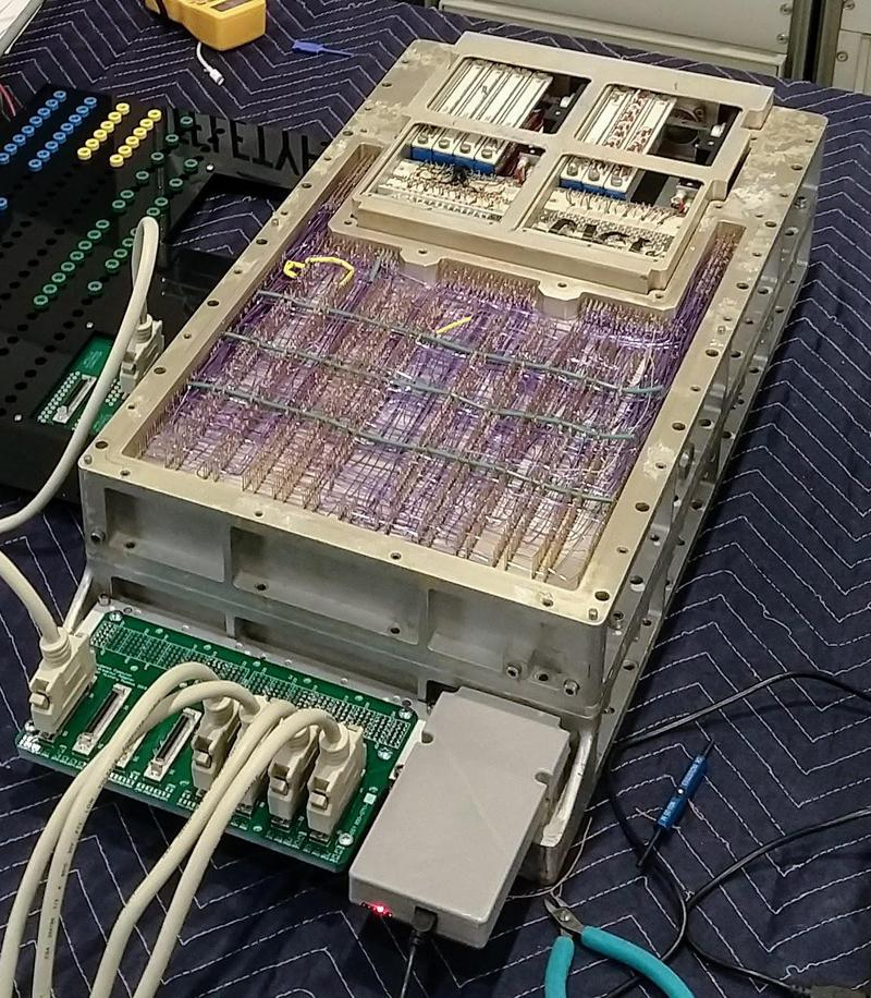 The Apollo Guidance Computer powered up. The cover is off, showing the computer's purple wire-wrap wiring of the backplane. We built the interfaces that are plugged into the front of the computer. At the back, vintage core rope simulator boxes are visible in the core rope slots.