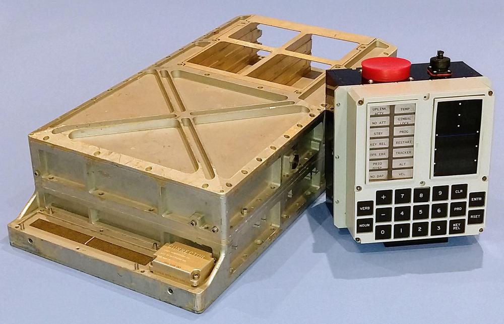 Our Apollo Guidance Computer and replica DSKY. The computer's I/O connectors are visible at the front of the computer. six core rope slots at the back are empty. The photo is an homage to this classic AGC photo.