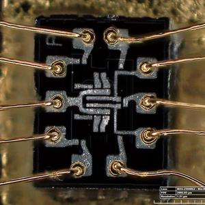 "Die photo of the dual 3-input NOR gate used in the AGC. Pins are numbered counterclockwise; pin 3 is to the right of the ""P"". Photo by Lisa Young, Smithsonian."