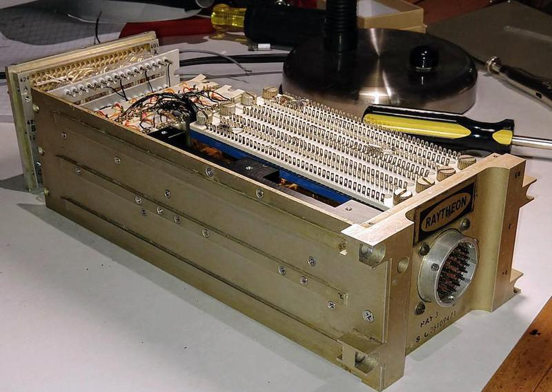 A rope simulator box, partially disassembled. The round external connector is visible at the right, and the pins to connect to the AGC at the left. Analog circuitry with cordwood construction is center-left. To the right, several Dipstik modules are visible, white with rows of pins.