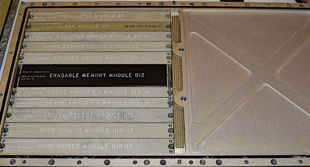 Tray B of the Apollo Guidance Computer. The erasable memory module is the large black module. Most of the other modules on the left are support for the erasable (RAM) and fixed (core rope) memory. The core rope modules would slide into the right hand side under the metal cover.