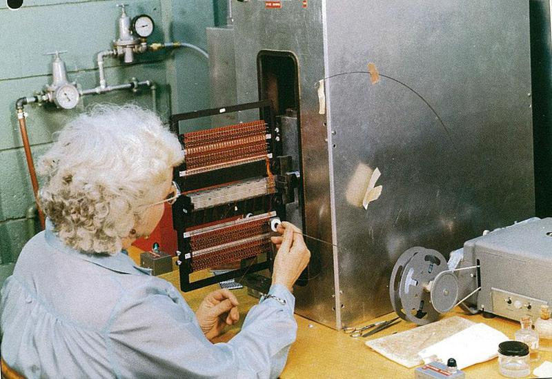A woman wiring sense lines in a core rope. She is threading the wire through a white circular aperture that indicates the core to wire. Source: Raytheon CN-4-20C / Smithsonian Institution WEB15435-2016.