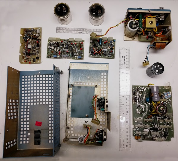 The Alto's switching power supply, disassembled. The main board is in the lower right. The three circuit boards are at top, below the large input capacitors.