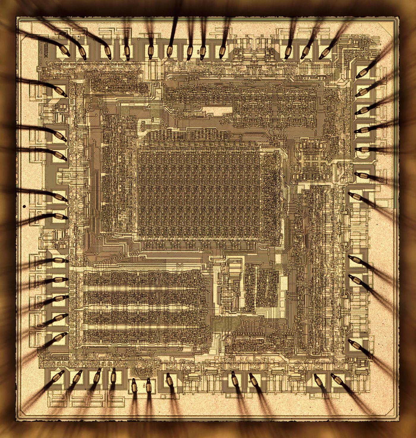 Die photo of the Am2901 chip. This image shows the metal layers of the chip; the silicon is underneath. Around the edges of the die, tiny bond wires connect the chip to the external pins. (Click the photo for a high-res image.)