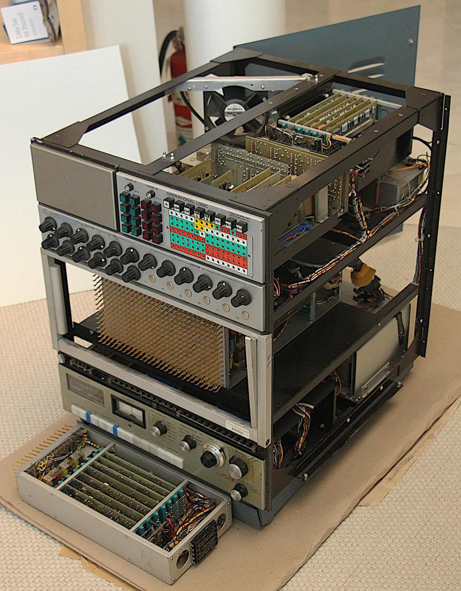The analog computer with the plugboard and sides removed to show the internal circuitry. The power supply is in the lower back section. One module has been removed and placed in front of the computer.