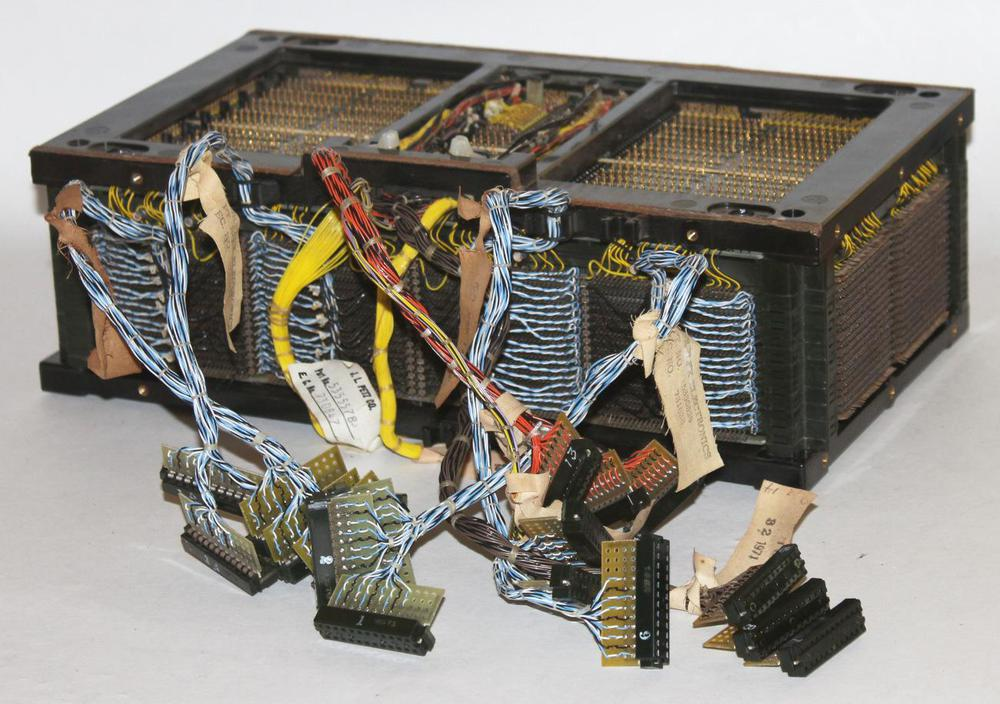A 64 KB core array from the IBM S/360 Model 50. There are 18 core planes stacked front-to-back. The blue cables are the sense/inhibit lines. Driver cards are plugged into the front of this array.