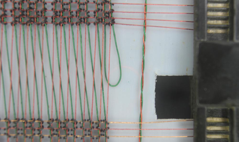 This closeup of the core plane shows the X and Y wires (red) and the sense wire (green) threaded through cores. Note that the sense wire shifts over two columns in the middle of the plane to reduce noise. Building planes with this shift used a patented manufacturing technique. Wires are connected to the frame of the core plane on the right.
