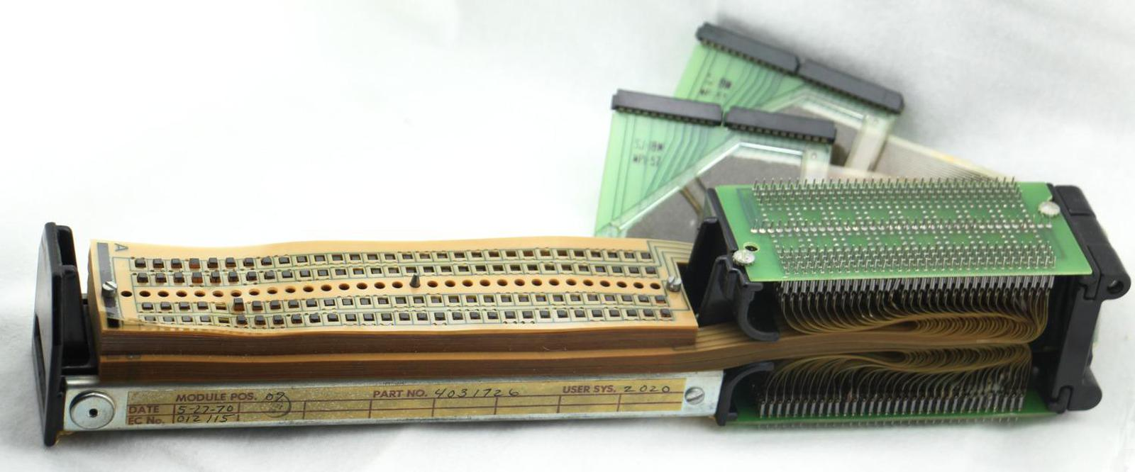 """A TROS module, about 15"""" (39 cm) long. On the left, 60 transformers pass through the stack of 128 Mylar sheets. (Only the square ends of the transformers are visible.) The sheets are connected to the diode boards on the right. The TROS module is connected to the rest of the computer through the connector cables at the back."""