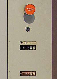 The Emergency Power Off knob shut down the entire system. Below it were the usage meters. The keyswitch selected the maintenance meter, so customers would not be charged for computer operation during maintenance.