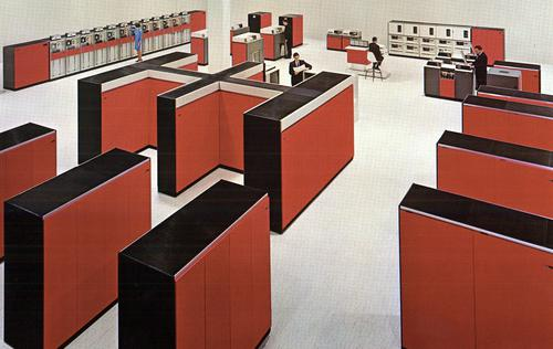 Large computer room with an IBM System/360 Model 85. The CPU, the double-H unit in the center, weighed over 7 tons.Cabinets in front are core memory storage, holding 256 kilobytes each. Cabinets on the right are I/O channels, connected to I/O devices at the back: tape drives, printers, disk drives, and card readers. Photo from IBM.