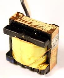 A copper band surrounds the ferrite core in the flyback transformer from an iPad charger.