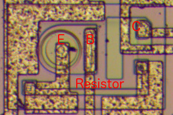This image shows one of the superbeta transistors in the LM308 op amp. Note the large, round emitter. The green rectangle below the transistor is a resistor.