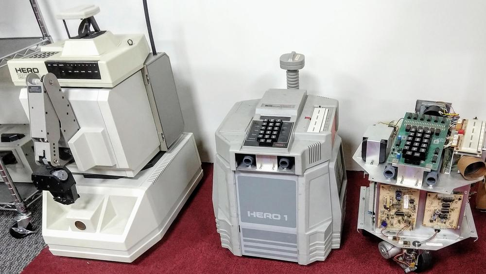 "Three Heathkit HERO robots. The HERO 2000 (1986, left) included multiple processors and speech synthesis, while the older HERO-1 robots have a single 6808 processor. The ""eyes"" are an ultrasonic distance sensor."