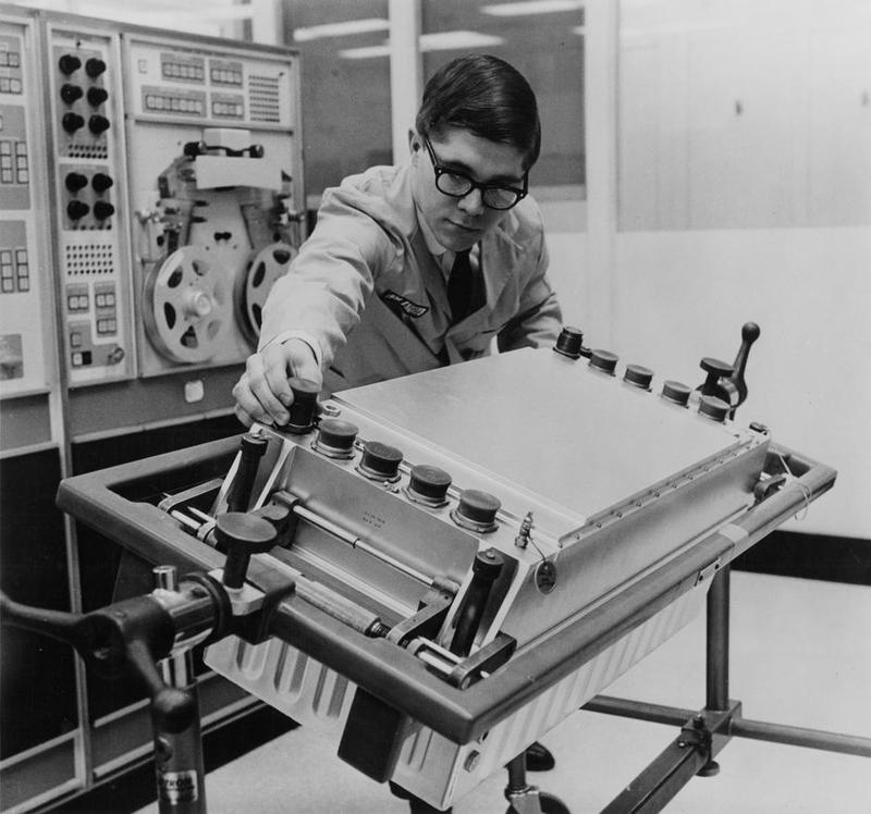 The LVDC mounted in a support frame for testing. Behind the operator is a test system called ACME (Aerospace Computer Manual Exerciser). The ACME paper tape reader is visible at the back. Photo from IBM.