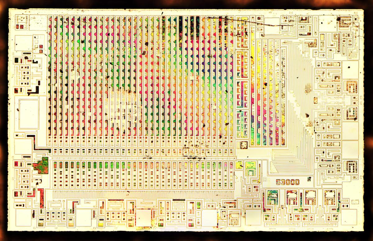 Die with the metal stripped off to expose the silicon. This makes the structure of the transistors visible. The thin remaining oxide layer produces a rainbow effect in some areas.
