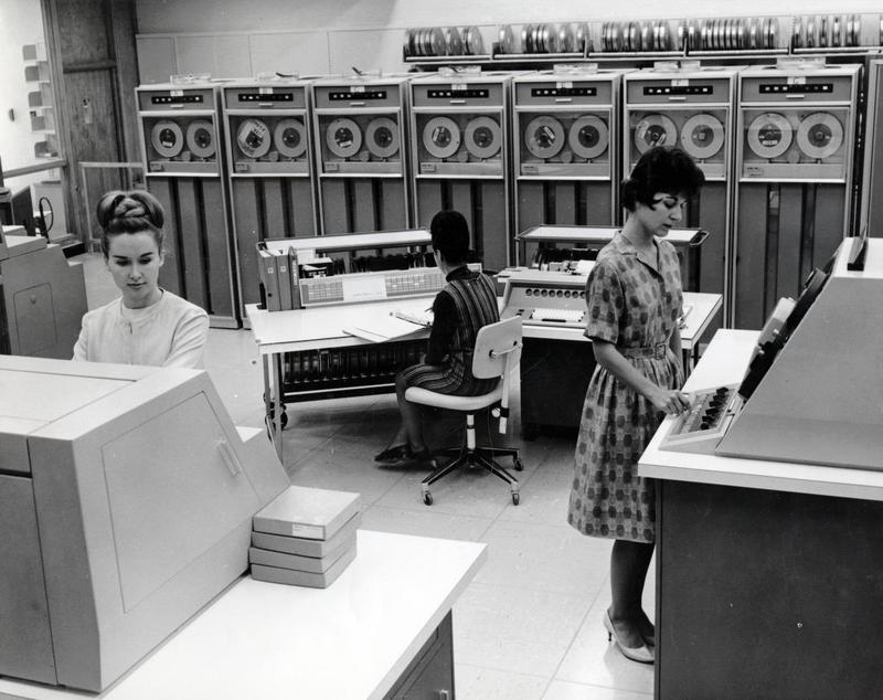 """Computer operators working with tape-driven Honeywell 800 mainframe computer."" The operators in this photo from the 1960s are presumably taking advantage of the special register groups unique to the Honeywell 800 and 1800 computers.  Photo from National Library of Medicine."