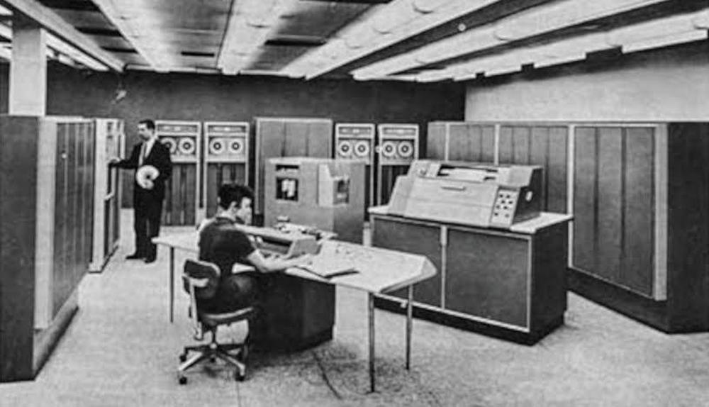 Honeywell 800 computer. The Central Processing Unit (containing special register groups) is in cabinets 6 feet high and 18 feet wide along the wall. The card reader and printer are in the center of the room. A typical system rented for $25,000 a month. Photo from BRL report, 1961 courtesy of Ed Thelen.