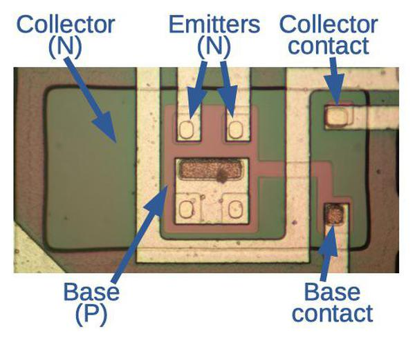 An input transistor on the integrated circuit die. The transistor is surrounded by an isolation ring (dark color) to separate it from the other transistors.