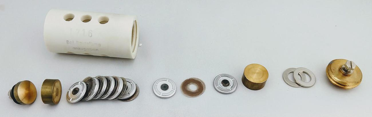 The spark gap disassembled, showing the stack of contact disks and mica insulators inside the ceramic tube.