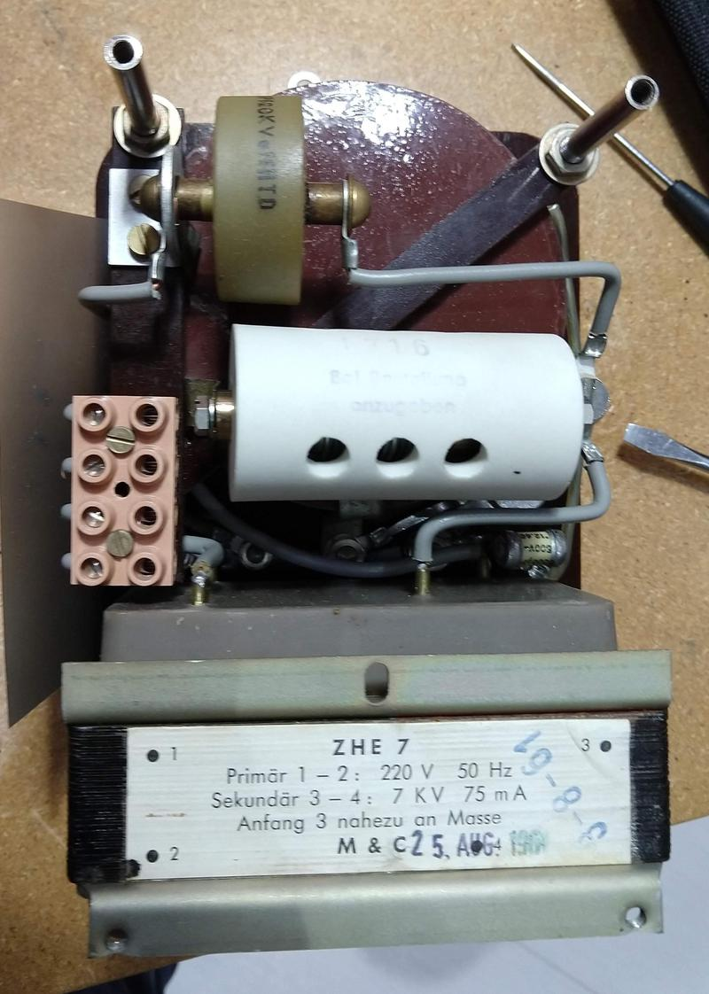 Inside the igniter. The output transformer (reddish round unit) is at the top with the yellowish tank capacitor above it. The ceramic spark gap is the cylinder in the middle. The pink Lego-link block is the safety interlock. The HV power transformer is at the bottom (label visible). T.