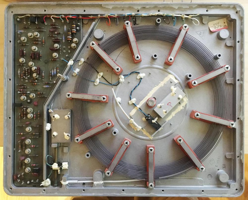 The coiled nickel wire inside a sonic delay has transducers at both ends (center and bottom left, with twisted wiring attached). To adjust the delay, the threaded rod (bottom left) moves the transducer's position along the wire. The metal boxes on the ends of the wires are dampers to prevent reflections. Photo courtesy of Alan Parker.
