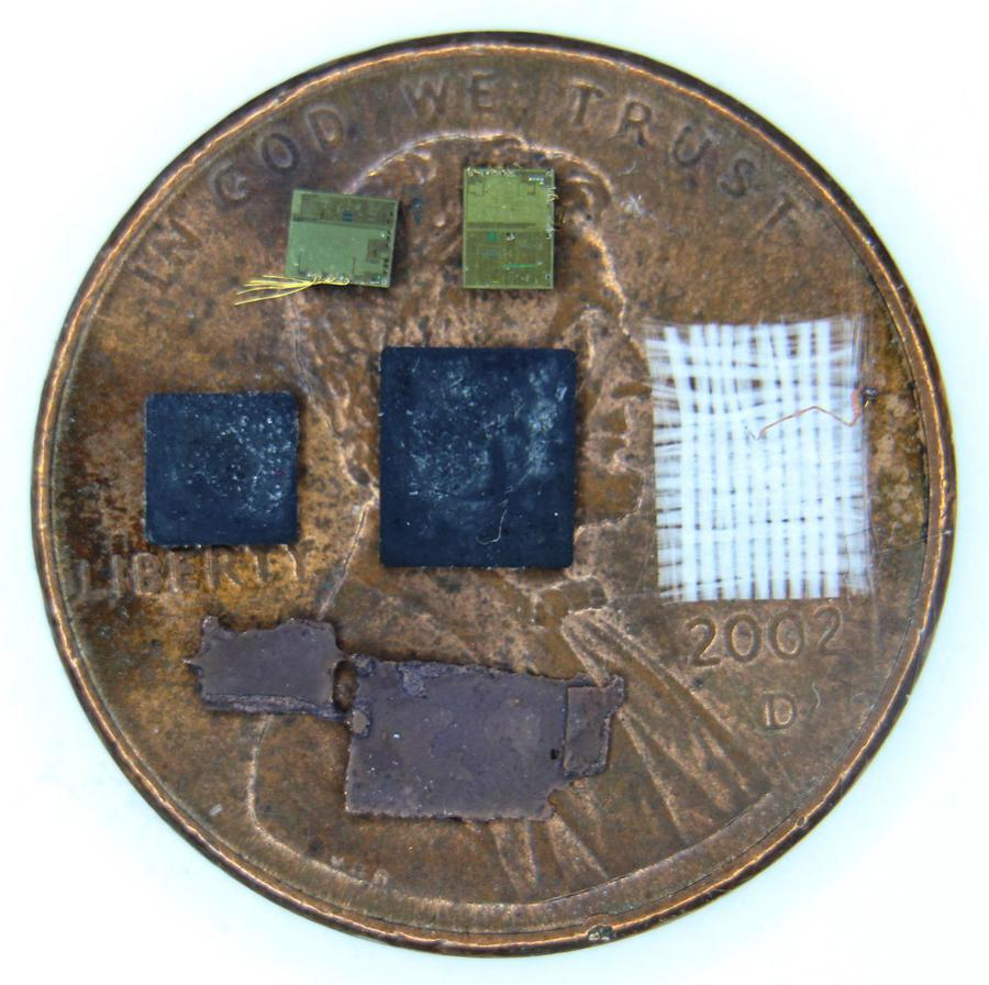 Components of the chip, on a penny for scale.