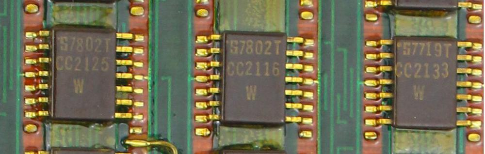Some of the chips used by the computer.  The PCB traces are visible in between the chips.  The 7802 date code indicates they were manufactured the second week of 1978.