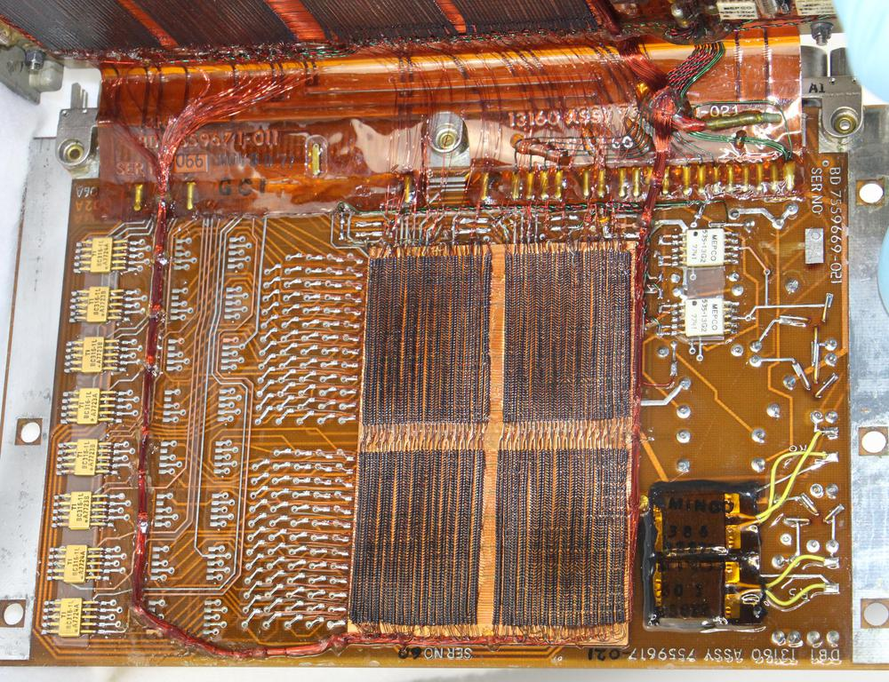 This board at the end of the core module has half of the regular core plane. Note the numerous connections to the left of the core; the 128 horizontal wires are connected to the circuit board here. The packages at the far left each hold 8 diodes.