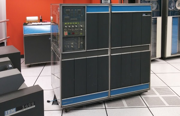 An IBM 1401 mainframe computer at the Computer History Museum. Behind it is the IBM 1406 Storage Unit, providing an additional 12,000 characters of storage. IBM 729 tape drives are at the right and an IBM 1402 Card Read Punch is at the far left.