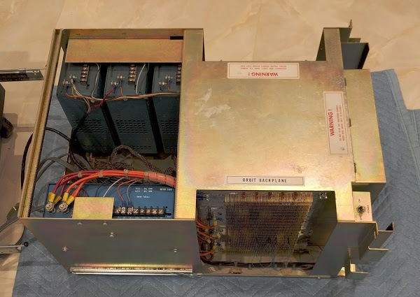 The Alto's chassis has been removed. On the left are the four switching power supplies (blue boxes). On the right, the connections for the wire-wrapped backplane are visible. The circuit boards plug into this backplane.