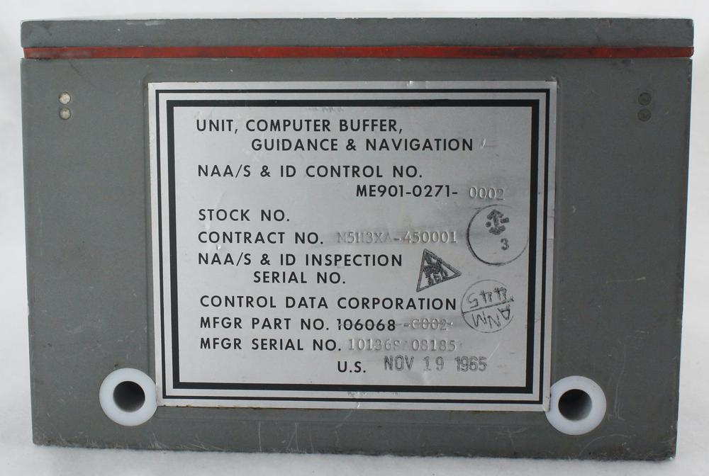 """Back of the Buffer Unit with identifying label and two holes for dagger pins. The labels say """"Unit, Computer Buffer Guidance & Navigation. NAA/S & ID Control No. ME901-0271-0002. Stock No. Contract No. M5H3XA-450001. NAA/S & ID Inspection Serial No. Control Data Corporation MFGR Part No. 106068-0002. Mfgr Serial No. 10136SA08185. US Nov 19 1965."""