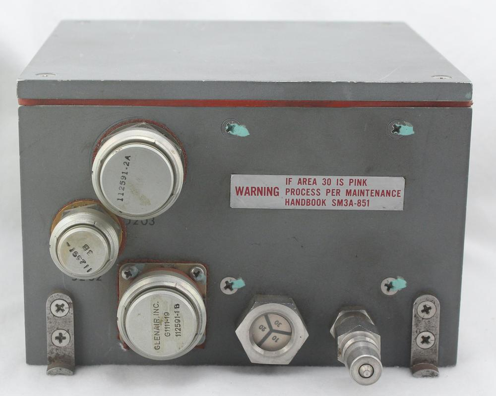"""The Computer Buffer Unit is a 4""""×6""""×6"""" box. The three electrical connectors on the left are covered by protective covers. It has a humidity indicator and pressurization valve at the bottom."""