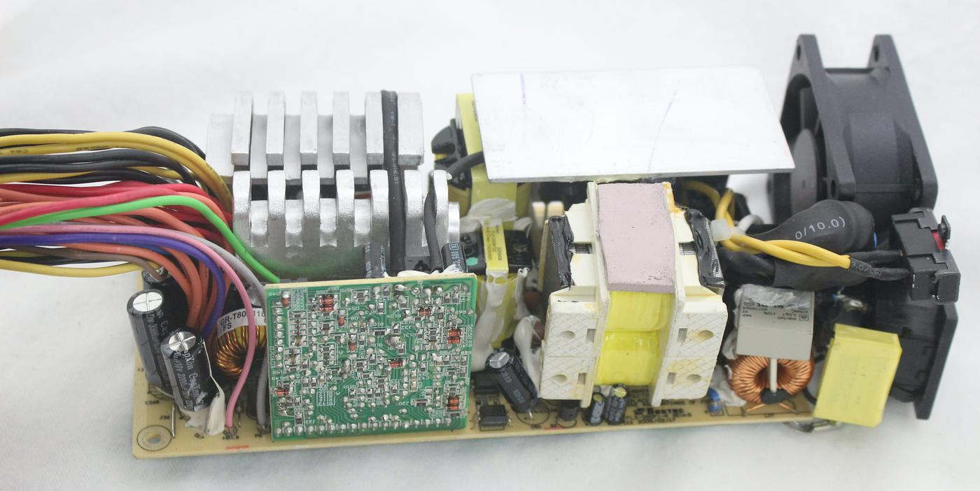 The power supply, removed from the case. The large bundle of wires at the left is connected to the computer.  The large component in the middle that looks like a transformer is a filter inductor. Click this photo (or any other) for a larger version.
