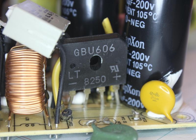 """The bridge rectifier is labeled """"GBU606"""". Filter circuitry is to its left. To the right, the large black cylinder is one of the voltage-doubler capacitors. The small yellow capacitor is a special Y capacitor, designed for safety."""