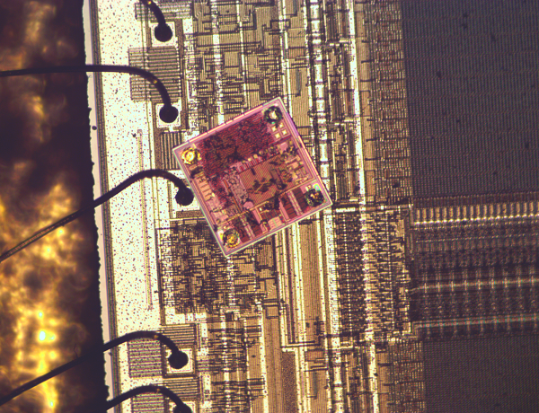 The Impinj Monza 4 RFID chip on top of a 8751 microcontroller chip shows that the RFID chip is very small and dense.