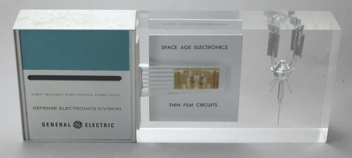 """The GE paperweight consists of circuitry and a satellite model encased in thick clear plastic. It is labeled """"Light Military Electronics Department, Defense Electronics Division, General Electric. Space Age Electronics, thin film circuits."""""""