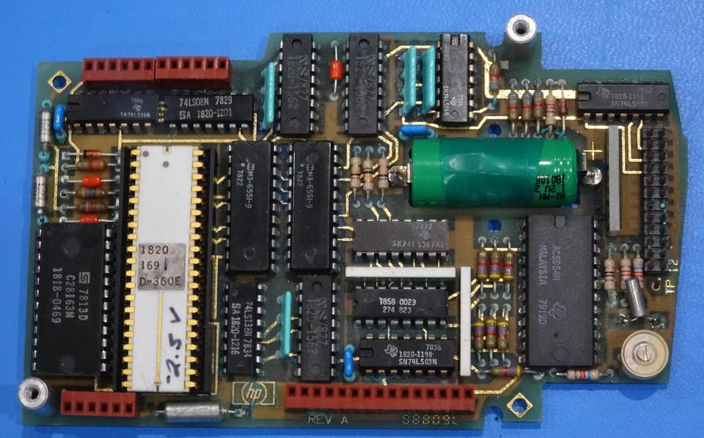 Nanoprocessor (white chip) as part of an HP clock module. Note the hand-written voltage on the chip; each chip required a different bias voltage. Photo courtesy of Marc Verdiell.
