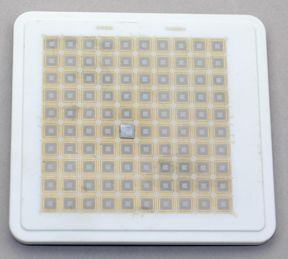 The ceramic substrate for a TCM, from the box. It is fairly small, measuring 11&times11.7 cm. This substrate holds 100 silicon dies; one is visible near the middle.