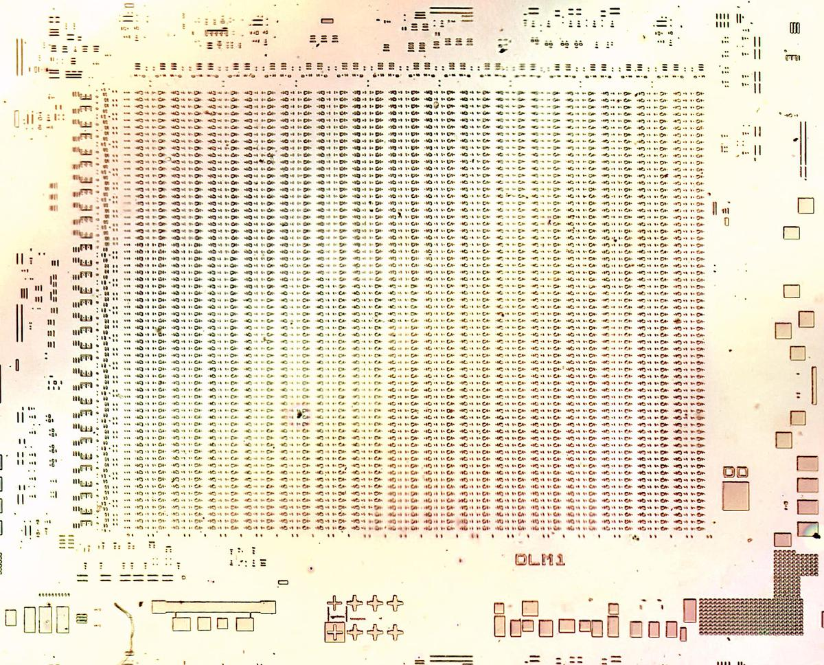 "Die photo of one of the memory chips on the wafer. It is only partially manufactured. The part number ""DLM1"" is visible on it."