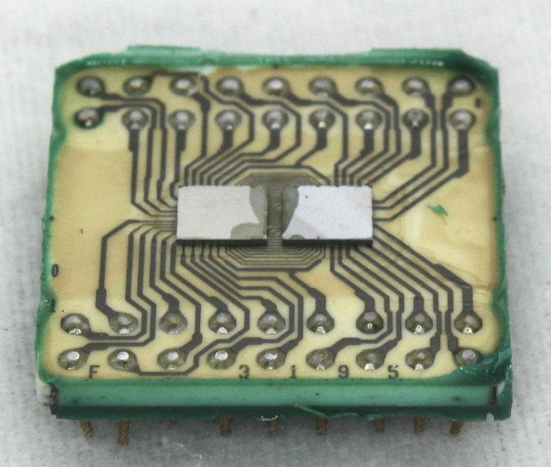 This IBM integrated circuit contains two silicon dies mounted on a ceramic substrate. Wiring printed on the substrate connects the dies to the pins underneath.